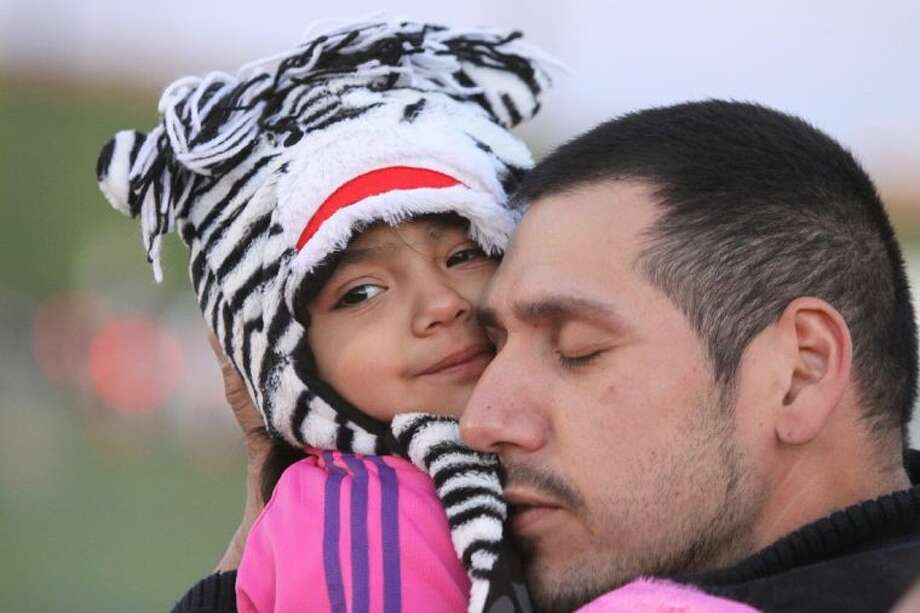 Michael Munoz of Houston cuddles with his daughter Caylie, 2, to help stay warm before the start of the 29th Annual BP MS 150 trek from Houston to Austin Saturday at Rhodes Stadium in Katy. Approximately 12,000 cyclists embarked on the two-day, 180-mile journey to drive awareness for a cure for multiple sclerosis. Photo: Alan Warren