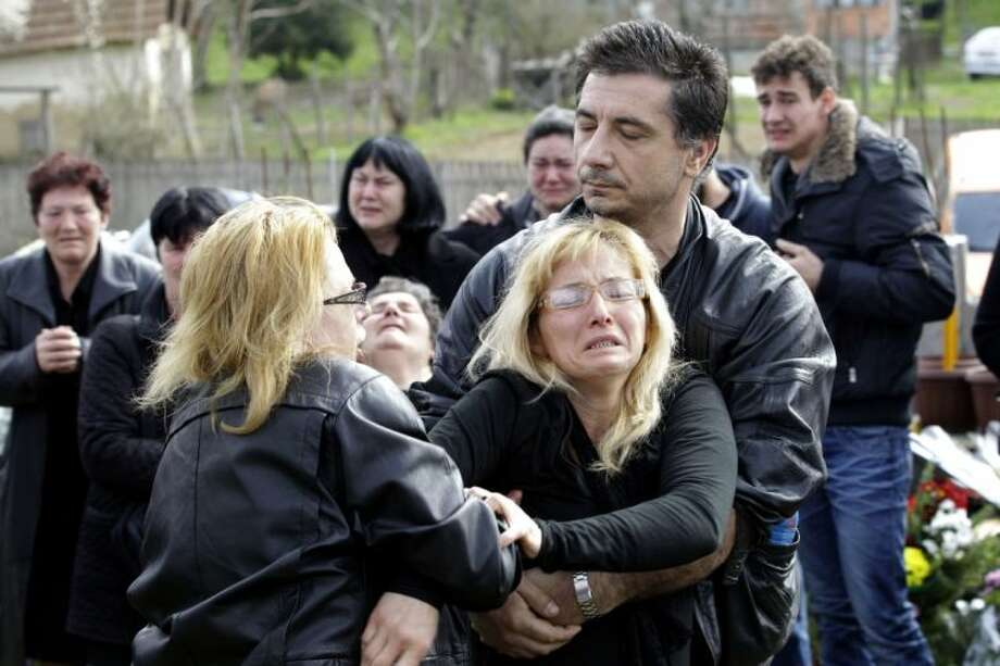 Relatives of victims of a shooting react prior to a mass funeral in the village of Velika Ivanca, some 30 miles southeast of Belgrade, Serbia Friday. Photo: Darko Vojinovic