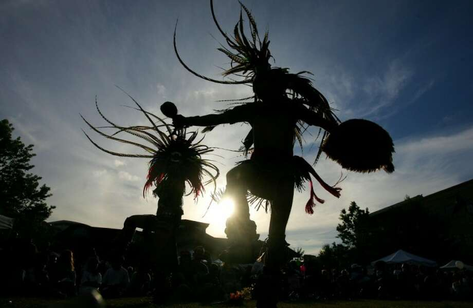Aztec dancers from the Conroe-based group, Chikawa, perform as the sun sets Wednesday at Market Street in The Woodlands at the Montgomery County Hispanic Chamber 8th Fiesta Universal.