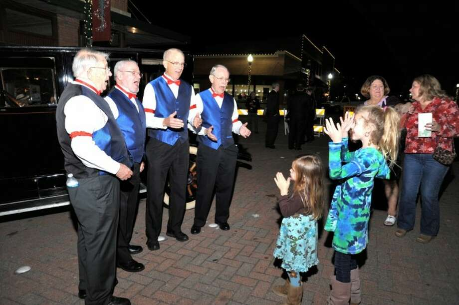 Youngsters enjoy the singing of the Silver Statesmen Barbershop Quartet at the 100th anniversary of the Gentry Building last November.