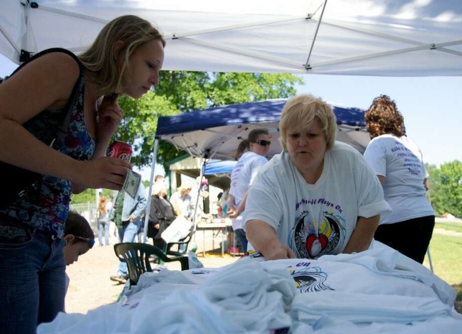 Jennifer Shipley, left, purchases a shirt in remembrance of Kala Schuchardt, from Robin Wright during a barbecue fundraiser for the family at the Willis Youth Athletic Association baseball fields in Willis. Shipley attended high school with Schuchardt and donated money to help the family. Photo: Staff Photo By Eric S. Swist