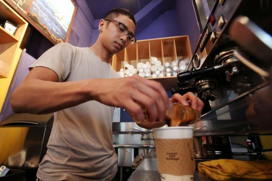 In this photo taken last Thursday, barista Michael Bledsoe prepares a two-shot coffee drink in a coffee shop in Seattle. The college class of 2012 is in for a rude welcome to the world of work. A weak labor market already has left half of young college grads either jobless or underemployed in positions that don't fully use their skills and knowledge. Photo: AP Photo By Elaine Thompson