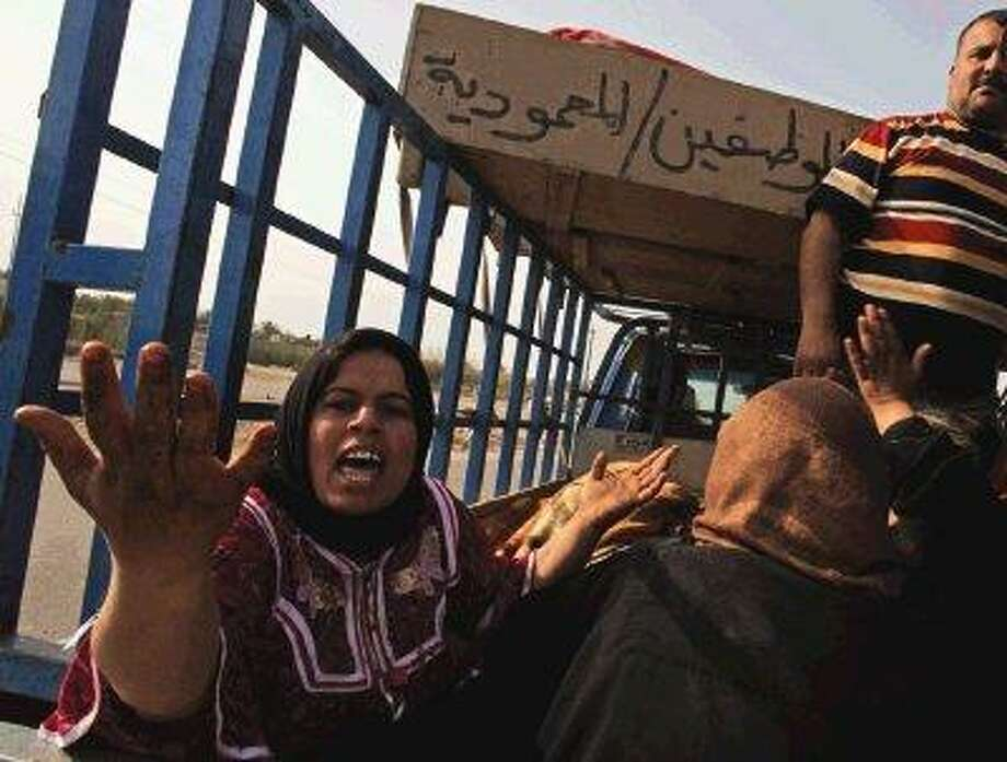 Mourner grieve as they ride with coffins of relatives killed in a village outside Baghdad, Iraq, Saturday. Gunmen in Iraqi military uniforms raided a village outside Baghdad and killed at least 24 people in an execution style attack, apparently targeting a Sunni group that revolted against al-Qaida and helped turn the tide of the Iraq war. / AP2010