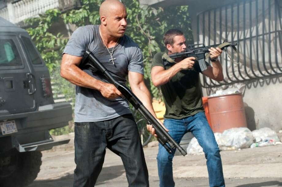 "In this film publicity image released by Universal Pictures, Vin Diesel, left, and Paul Walker are shown in a scene from ""Fast Five."""