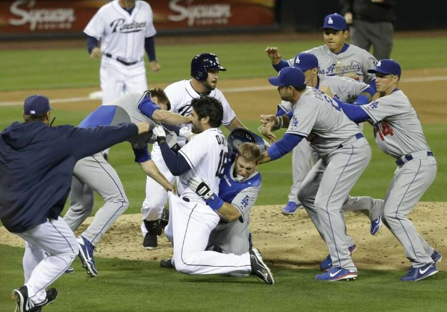 The San Diego Padres' Carlos Quentin (middle) charges into Dodgers pitcher Zack Greinke after being hit by a pitch in the sixth inning. Greinke is out with a broken collarbone and Quentin has been suspended for eight games. Photo: Lenny Ignelzi