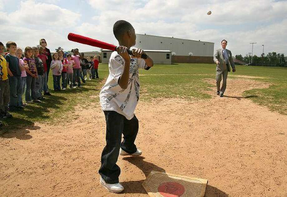 Willis WildKat baseball players, from left, Tyler Hatcher, Ross King, Michael Corbett and Omar Rodriguez offer batting stance pointers to second-grader Aaron Hecox.