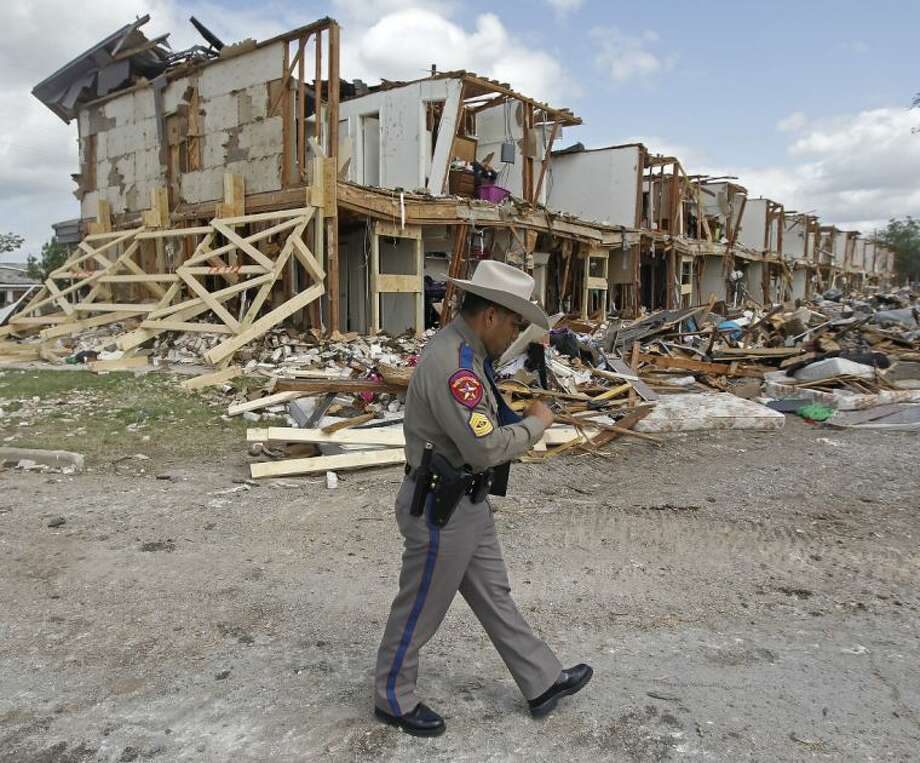 Texas Department of Public Safety Sgt. Jason Reyes walks past a damaged apartment complex, Sunday, April 21, 2013, four days after an explosion at a fertilizer plant in West, Texas. The massive explosion at the West Fertilizer Co. Wednesday night killed 14 people and injured more than 160. (AP Photo/The Dallas Morning News, Michael Ainsworth, Pool) Photo: Michael Ainsworth