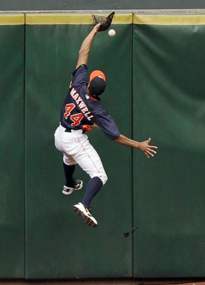 Astros center fielder Justin Maxwell goes high on the wall but cannot make the catch giving Cleveland Indians' Yan Gomes a triple. The Astros lost 5-4. Photo: Pat Sullivan