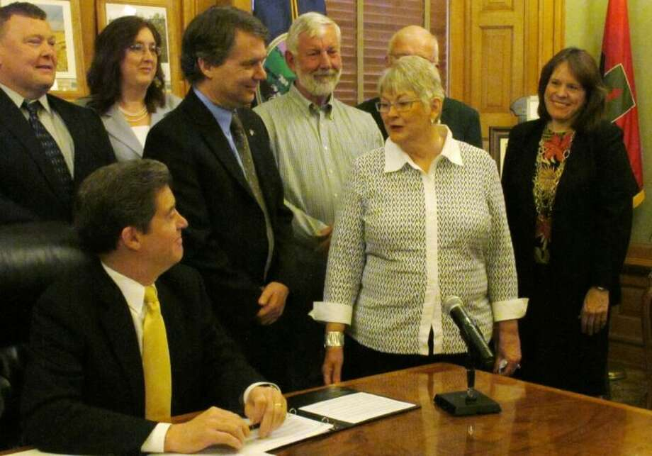 Mary Lou Rusco, second from right, a Wichita resident whose leukemia was treated in 2009 with cells from umbilical cord blood, discusses her experience with Gov. Sam Brownback, lower left, Monday, April 22, 2013, at the Statehouse in Topeka, Kan. Brownback has signed legislation creating a new Midwest Stem Cell Therapy Center at the University of Kansas Medical Center in Kansas City. Photo: John Hanna