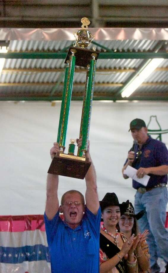 """Don Canterbury, of We """"B"""" Smokin' cookers, hoists the grand champion trophy over his head after being announced as the 2012 Montgomery County Fair and Rodeo Barbecue Cook-Off contest grand champion for the third time. Photo: Staff Photo By Eric S. Swist"""