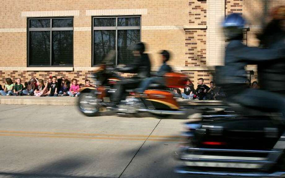 Austin Elementary School students watch as classmates fly past on the back of motorcycles belonging to members of the Cut-N-Shoot Harley Owners Group. Nearly 300 first -through fourth-graders took part Friday in the school's annual Excel to Ride program sponsored by the enthusiast group. / The Courier