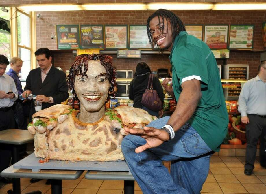 In this photograph taken by AP Images for SUBWAY, newest SUBWAY Famous Fan Robert Griffin III, top prospect in the 2012 NFL Draft, poses with his life-size statue made of SUBWAY Smokehouse BBQ Chicken Tuesday in New York. Photo: Diane Bondareff