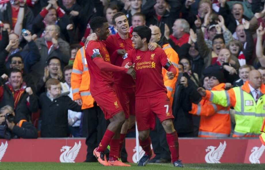Liverpool's Luis Suarez, right, celebrates with teammates after scoring against Chelsea during an English Premier League soccer match at Anfield Stadium on Sunday in Liverpool, England. Suarez scored a last-minute equalizer in a 2-2 draw after having earlier bitten an opponent's arm in a second-half incident. Photo: Jon Super