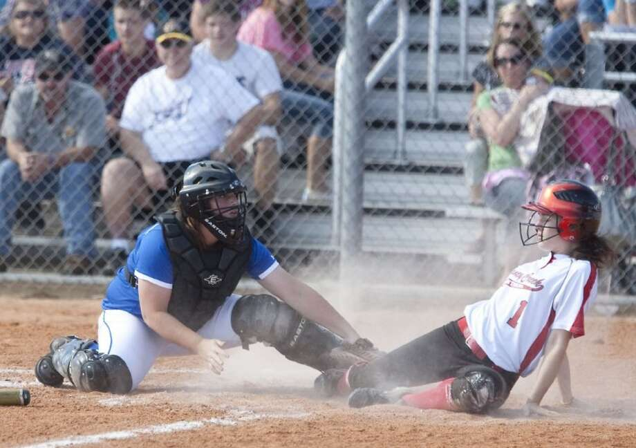 New Caney catcher Brittany Mussett tags out Hayley Eighmy at home plate during the fifth inning of a playoff seeding team out of District 18-4A on Monday at Porter High School. Photo: Karl Anderson