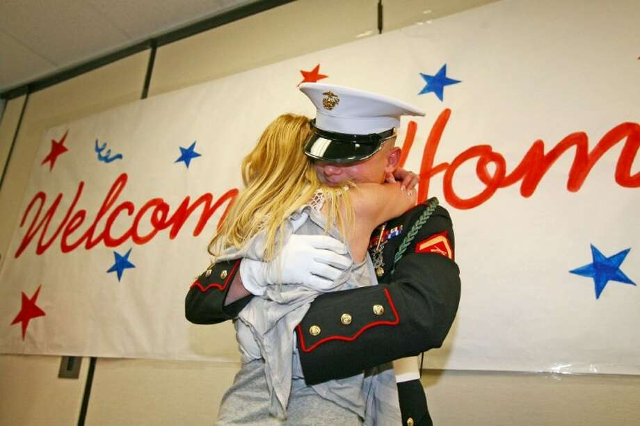 Lance Cpl. Rick Menard hugs his sister He'aven Friday at Knox Junior High School in The Woodlands. Menard, a U.S. Marine, recently returned from Afghanistan but kept it a secret to surprise his sister.