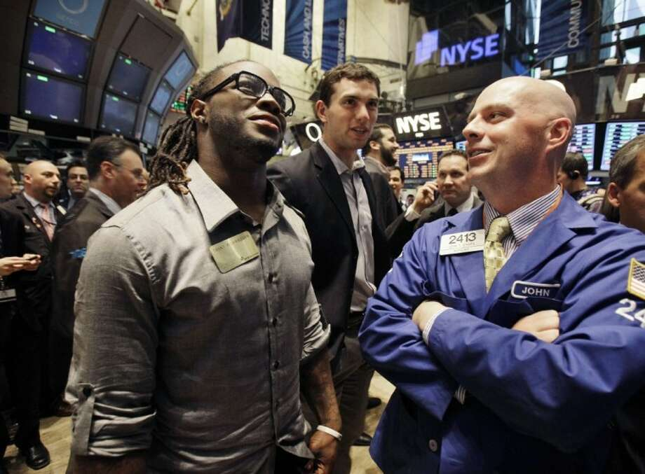 NFL draft prospects Trent Richardson, left, and Andrew Luck, center, talk with specialist John O'Hara during their visit Wednesday to the trading floor of the New York Stock Exchange. Photo: Richard Drew