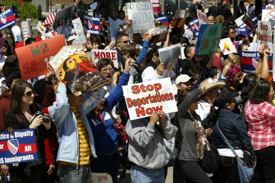 """Supporters of immigrant rights rally at the Supreme Court in Washington Wednesday as the court held a hearing on Arizona's """"show me your papers"""" immigration law. Photo: Charles Dharapak"""