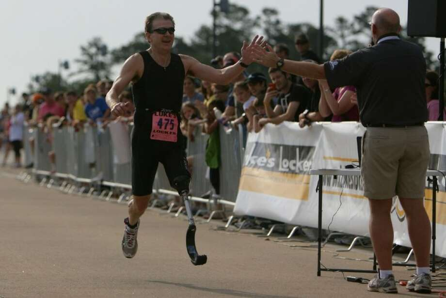 Triathlete Chris Arthey, of The Woodlands, high fives event M.C. Jon Walk as he pushes towards the finish during Saturday's CB&I Triathlon in The Woodlands.