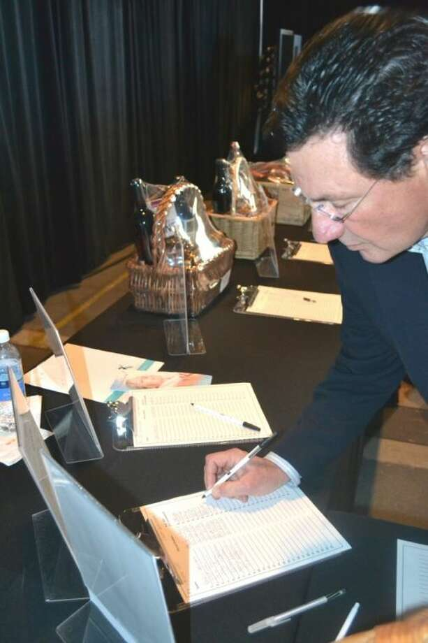 Wine dinner attendee Brian Arnold bids on a one night stay at the Hyatt and tickets to a Diana Krall concert Sunday night at The Pavilion Partners 15th Annual Wine Dinner and Auction.