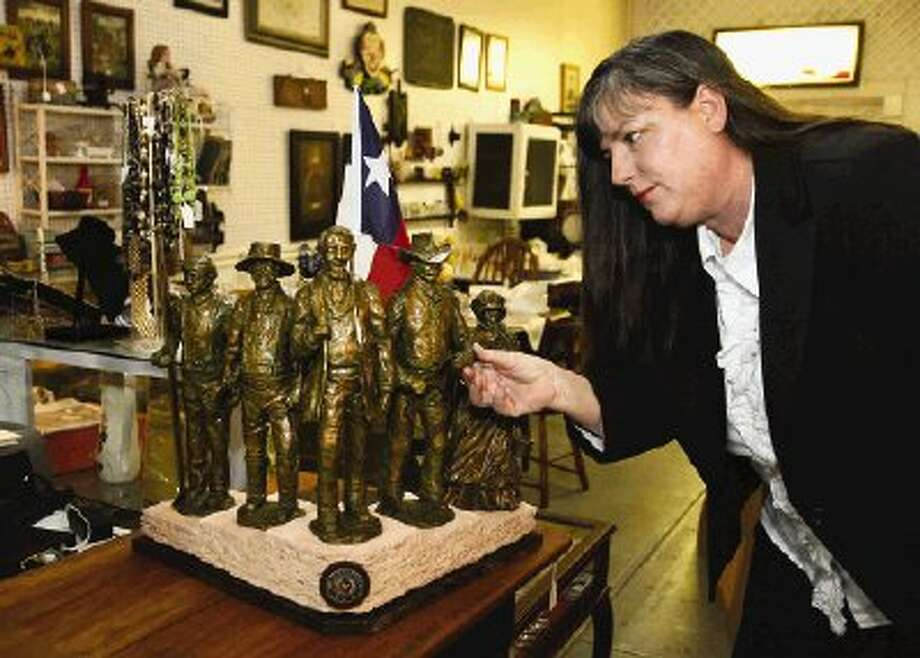 """Montgomery artist Lynn Peverill examines one of the preliminary models of for the life-size """"Pioneers of Montgomery"""" statue planned for Cedar Brake Park."""