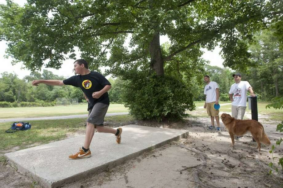 Austin Soileau throws a disc on the disc golf course at McDade Park in Conroe on Sunday. Photo: Karl Anderson