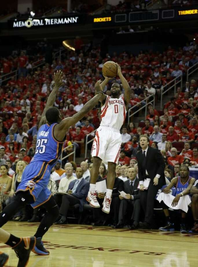 The Houston Rockets' Aaron Brooks shoots over Oklahoma City's DeAndre Liggins in the Rockets' 105-103 victory on Monday night. The Rockets trail the series 3-1. Photo: David J. Phillip