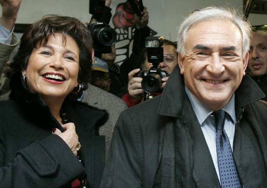 """In this Nov.16, 2006 file photo, Dominique Strauss-Kahn with his wife Anne Sinclair, smile after voting in Sarcelles, outside Paris. Since their marriage in 1991, the wife of jailed IMF chief Dominique Strauss-Kahn has steadfastly defended her husband through multiple political and financial scandals, """"with tooth and claw"""" as she once told a French news magazine. Now the former star television interviewer and wealthy heiress is faced with the most searing test of her loyalty yet, as she stands by her man amid accusations he tried to rape a hotel maid."""