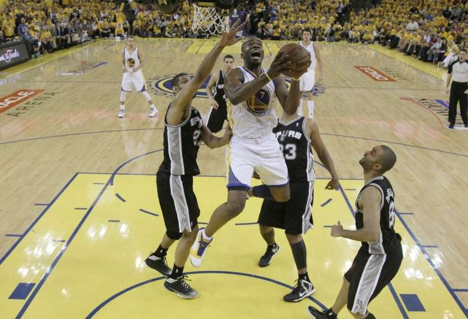 Golden State Warriors forward Carl Landry shoots against San Antonio Spurs forward Tim Duncan, left, center Boris Diaw, second from right, and guard Tony Parker during the second half. The Warriors won 97-87 in overtime. Photo: Marcio Jose Sanchez