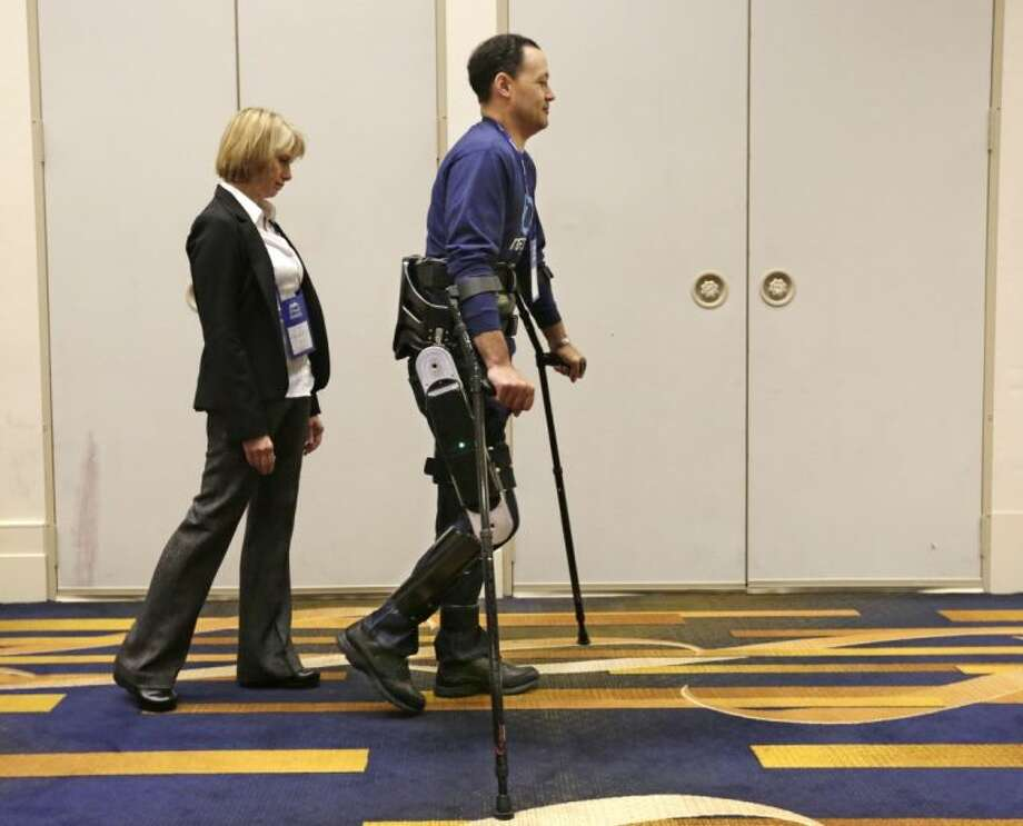 In this May 6, 2013 photo, Michael Gore, center, who is paralyzed from a spinal injury, walks with the use of the Indego wearable robot under the supervision of physical therapist Clare Hartigan during a meeting of the American Spinal Injury Association at a downtown hotel in Chicago. Eleven years ago, Gore was paralyzed from the waist down in a workplace accident, but with the aid of the 27-pound gadget that snaps together from pieces that fit into a backpack he stands and walks with the assistance of science and engineering. The device is among several competing products that hold promise for people with spinal injuries, like Gore, and for people with multiple sclerosis and cerebral palsy or for those recovering from strokes. (AP Photo/M. Spencer Green) Photo: M. Spencer Green