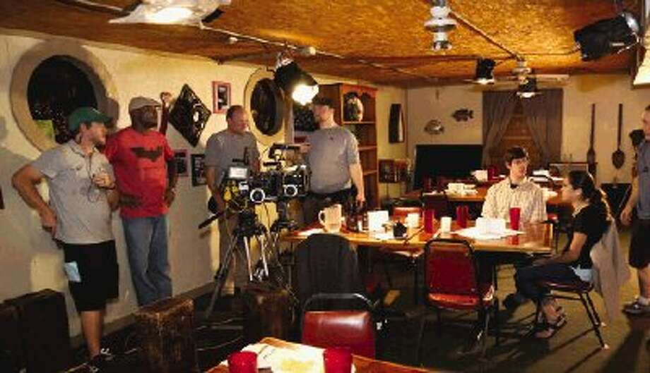 """Production crews prepare the lights and camera before shooting a scene for the movie """"Sacrifice"""" at Canada's Hole in the Wall Grill in Conroe Thursday."""
