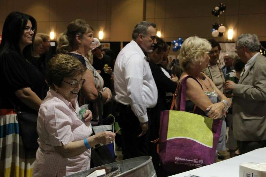 A woman smiles while looking at her raffle ticket during a raffle-calling Thursday night, surrounded by a crowd of other attendees, at Conroe's annual Tastefest. Photo: Photo By Megan 0'Sullivan