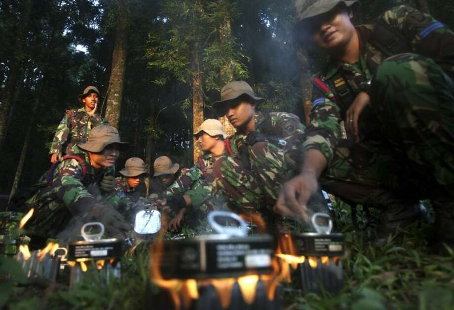 Indonesian soldiers mobilized for search of a missing Russian plane cook food at Taman Nasional Halimun Salak in Sukabumi, West Java, Indonesia, this morning. Search and rescue teams were scouring the slopes of a dormant volcano in western Indonesia early Thursday for signs of a new Russian-made passenger plane that dropped off the radar while on a demonstration flight Wednesday. Photo: Achmad Ibrahim