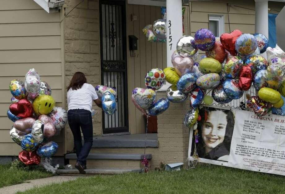 Culema Nevarez adds balloons to a growing tribute outside the home of Gina DeJesus in Cleveland Friday. DeJesus was freed Monday from the home of Ariel Castro, where she and two other women had been held captive for nearly a decade. Photo: Mark Duncan