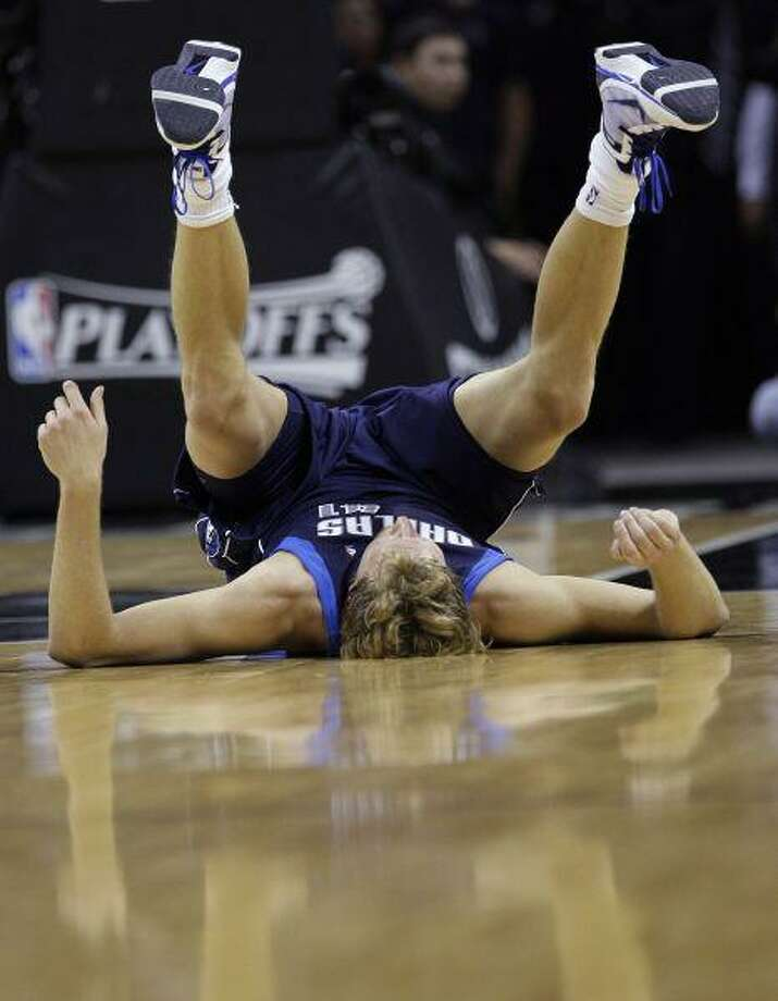 Dallas' Dirk Nowitzki falls down after his shot was blocked by San Antonio's Antonio McDyess during the first quarter of Game 6 Thursday in San Antonio. / AP2010