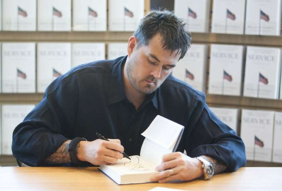 """Former Navy SEAL Marcus Luttrell signs copies of his memoir, """"Service: A Navy SEAL at War,"""" Monday at Barns & Noble in The Woodlands. Photo: Karl Anderson"""