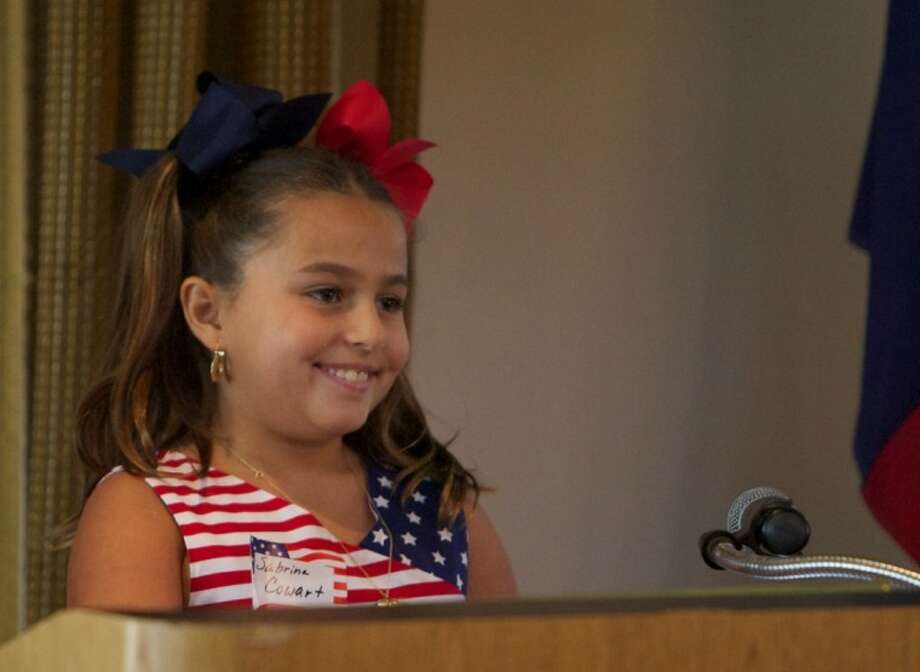 Turner Elementary School student Sabrina Cowart smiles as she stands at the podium after reading a portion of her essay to members of the Lake Conroe Area Republican Women at the Walden Yacht Club in Lake Conroe. Cowart won first place for her essay about Helen Keller. Photo: Staff Photo By Eric Swist