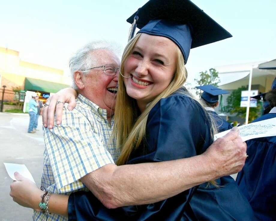 Mara Burnstad hugs her grandfather, Bill Sbordon, before the College Park High School graduation ceremony Tuesday at the Cynthia Woods Mitchell Pavilion.
