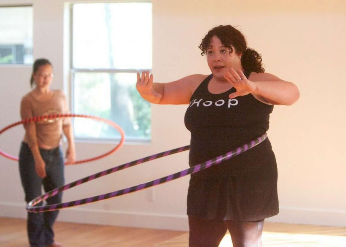 Hoopnotica instructor Heather Says teaches a group some basic hoop movements during a class at the Yoga Studio of The Woodlands.