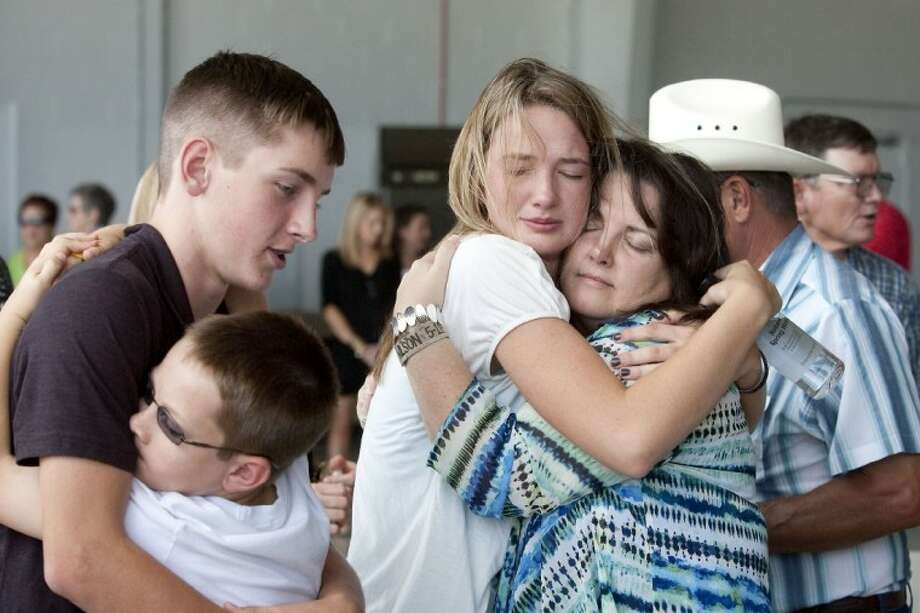 Mother Cindy Easterling, right, and sister Layne Wilson, along with brother Curtis Wilson and nephew Jaydon Wilson, embrace after the arrival of the body of Marine Sgt. Wade D. Wilson, 22, of Leon County, Friday at the Lone Star Executive Airport in Conroe. Wilson died May 11 while conducting combat operations in Helmand province, Afghanistan. See more photos online at yourhoustonnews.mycapture.com. Photo: Karl Anderson
