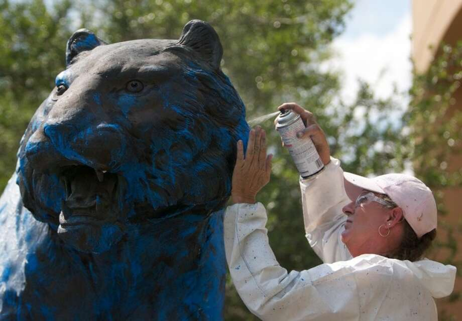 Custodial department employees with the Conroe Independent School District wash blue spray paint off of the Grady Spikes Memorial Tiger statue at Conroe High School May 16. Photo: Staff Photo By Eric Swist
