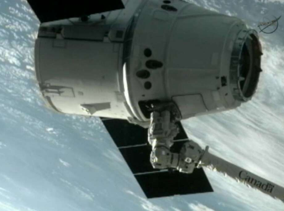 This image provided by NASA-TV shows the SpaceX Dragon commercial cargo craft after Dragon was grappled by the Canadarm2 robotic arm and connected to the International Space Station Friday. Dragon is scheduled to spend about a week docked with the station before returning to Earth on May 31 for retrieval. Photo: Uncredited
