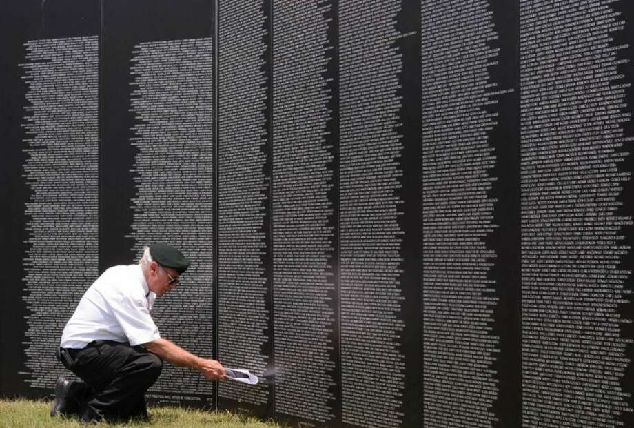 Special forces veteran John Householder looks through some of the 58,000 names of fallen soldiers on the traveling replica of the national Vietnam Veterans Memorial Wall on exhibit at the West, Texas fair grounds Thursday. Photo: Rod Aydelotte