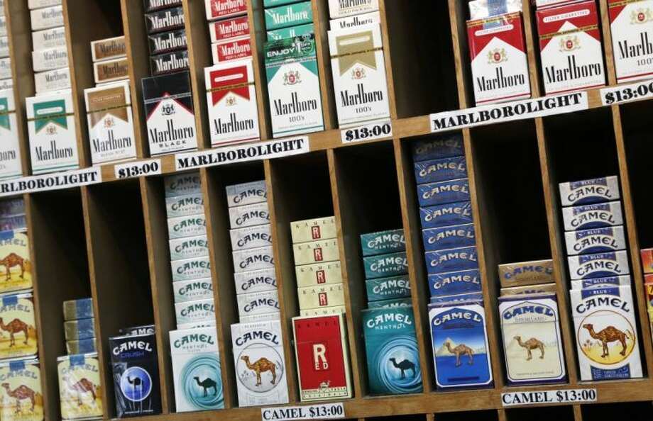Cigarette packs are displayed at a convenience store in New York, Monday, March 18, 2013. A new anti-smoking proposal would make New York the first city in the nation to keep tobacco products out of sight in retail stores. Mayor Michael Bloomberg says the goal is to reduce the youth smoking rate. The legislation would require stores to keep tobacco products in cabinets, drawers, under the counter, behind a curtain or in another concealed spot. They could only be visible when an adult is making a purchase or during restocking. (AP Photo/Mark Lennihan) Photo: Mark Lennihan