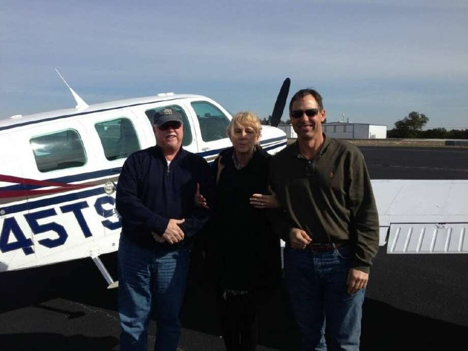 Pilots Pete Perez, left, and Mark Moran, right, both from The Woodlands, pose for a picture with a patient of M.D. Anderson. The pilots provide free air transportation for patients in need of medical care each year.