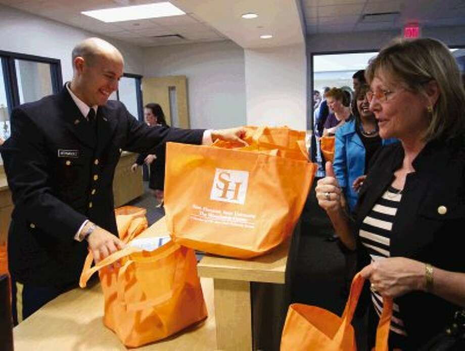 David Hernandez hands out goodie bags to visitors during the grand opening celebration for Sam Houston State University - The Woodlands Center on Wednesday. Photo: Staff Photo By Eric Swist