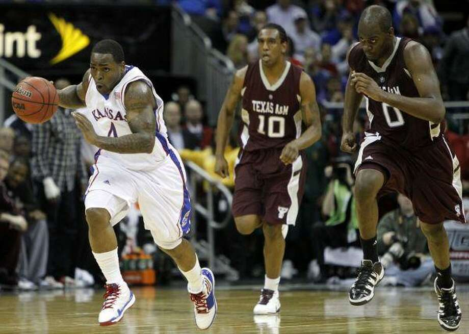 Kansas guard Sherron Collins (4) fast-breaks ahead of Texas A&M forwards Bryan Davis (0) David Loubeau (10) during the second half at the Big 12 tournament Friday in Kansas City, Mo. / AP2010