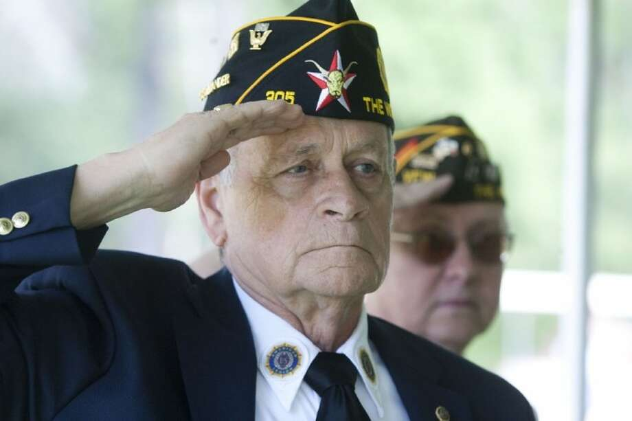 Pete Koch, a Navy veteran and commander of American Legion Post 305, salutes during a Memorial Day ceremony at Forest Park Funeral Home in The Woodlands. Photo: Karl Anderson