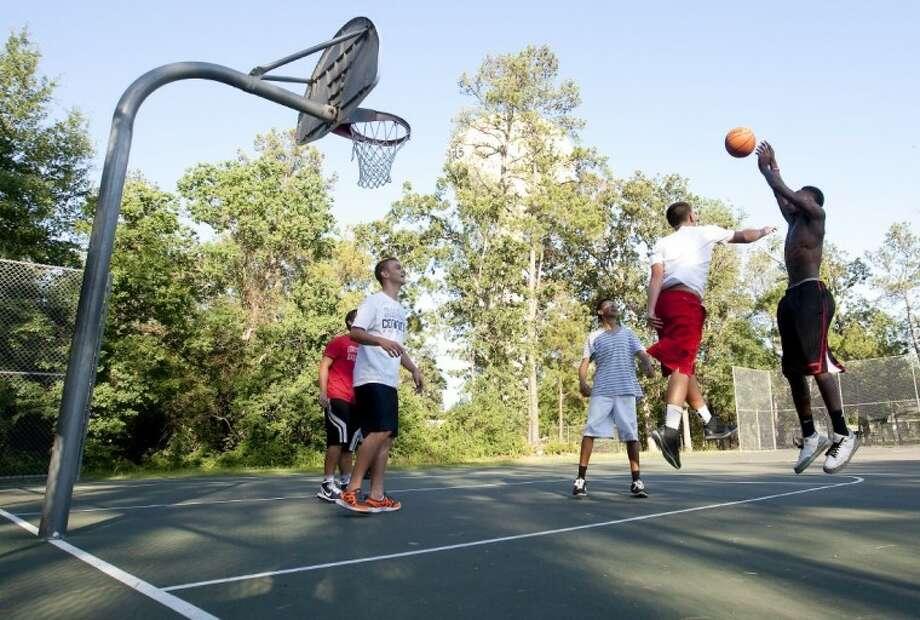 Park vistors play basketball at Lions Park in Conroe on Friday. Photo: Karl Anderson