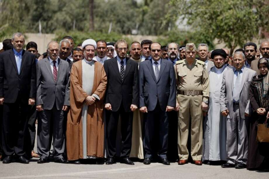Iraqi Prime Minister Nouri al-Maliki, center right, Iraqi acting Defense Minister Sadun al-Dulaymi, center left, government officials, and parliament members, attend the funeral procession of five slain soldiers at the headquarters of the Iraqi Ministry of Defense in Baghdad, Iraq, Sunday. Photo: Hadi Mizban
