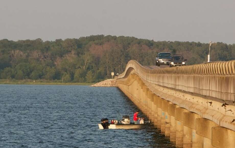 Anglers try their luck fishing near support pylons on the FM 1097 bridge on Lake Conroe. Photo: Staff Photo By Eric Swist